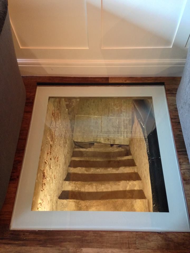 Square glass floor that reveals historic stairs