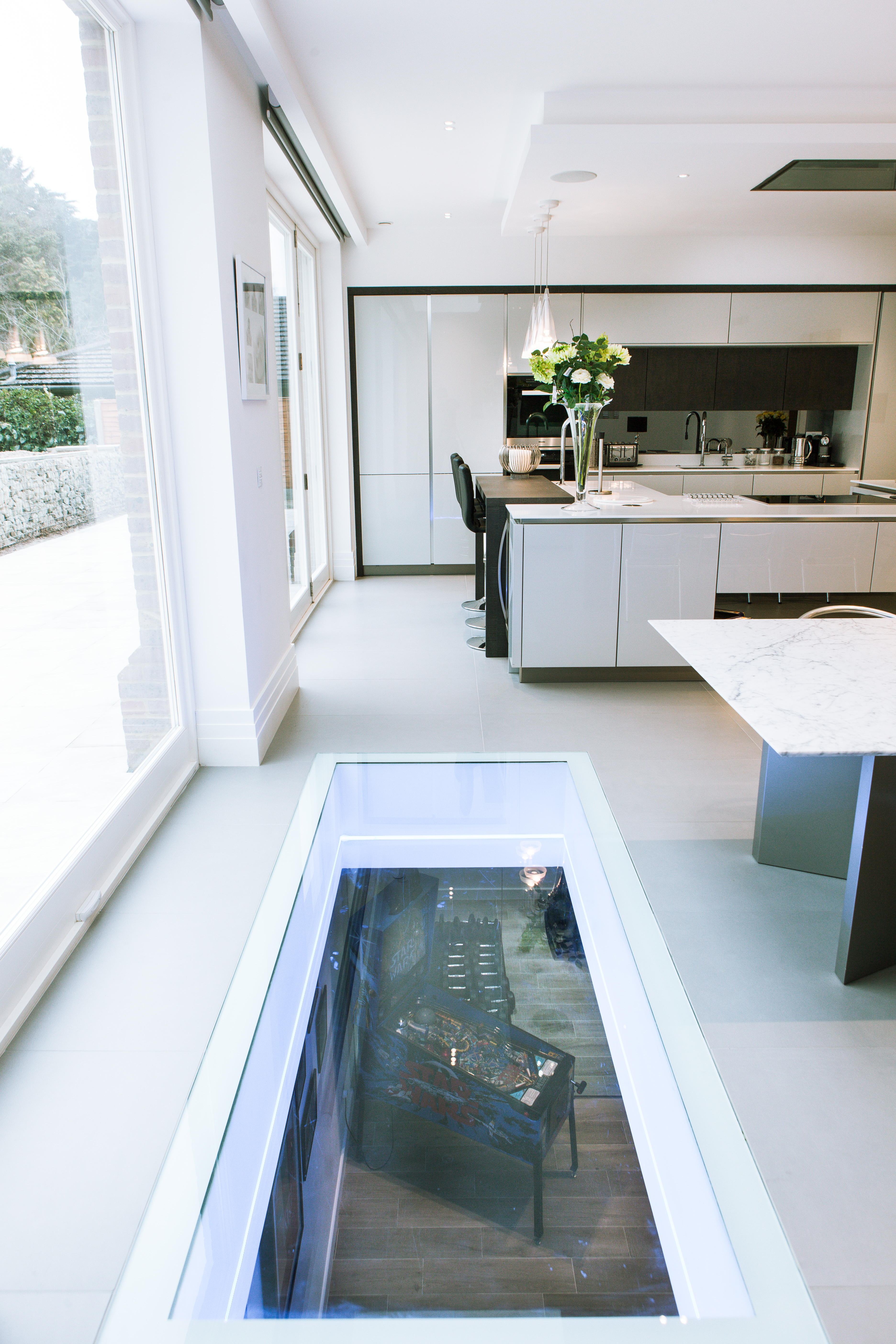 Oblong glass floor with white edge trim in modern kitchen